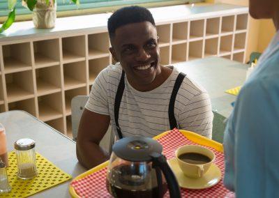 Waitress serving black coffee to man
